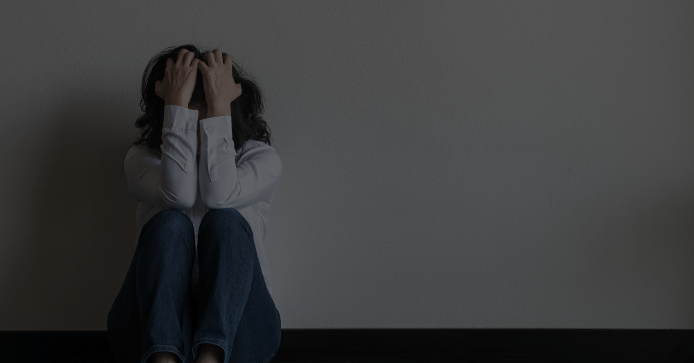 A distressed woman sitting against a wall covering her face